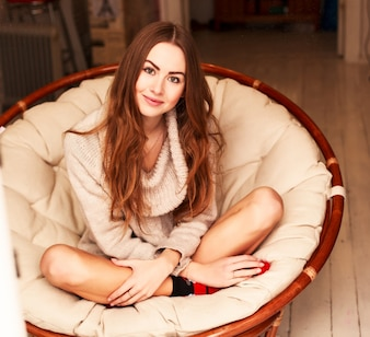Smiling young woman sitting in armchair