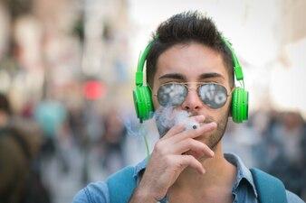 ヘッドフォンで若い男を喫煙し、城を設定する