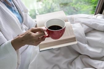 古い本とコーヒーとコピースペースのカップでベッドに女性のソフト写真