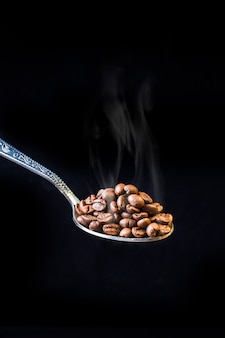 Spoon with freshly roasted coffee beans