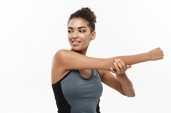 Sport, training, lifestyle and Fitness concept - portrait of beautiful happy African American woman stretching hands. Isolated on white studio background.