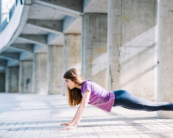 Sportive girl working out doing push ups