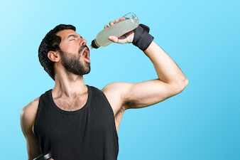Sportman doing weightlifting drinking water soda on colorful background