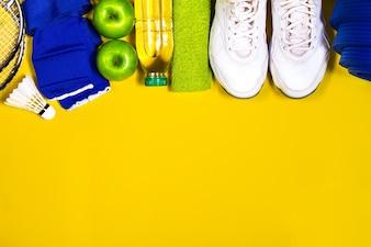 黄色のテーブルの上にフルーツと水とスポーツ器具