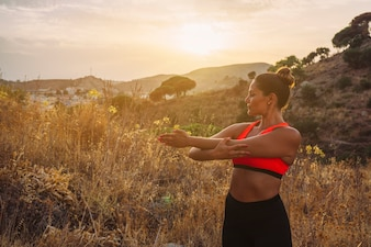 Sportswoman stretching with a beautiful landscape
