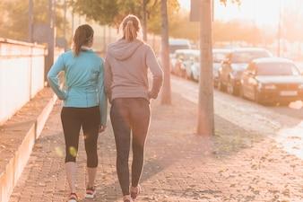 Sportswomen walking at sunset