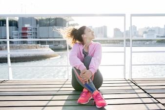 Sporty Girl Enjoying Listening to Music on Quay