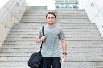 Sporty Man With Gym Bag and Water on Stairs