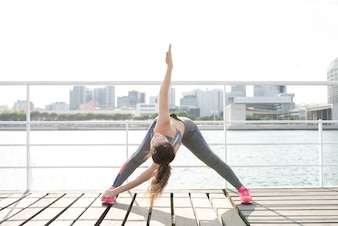 Sporty Woman Practicing Yoga on City Quay