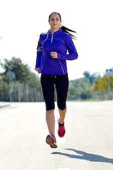 Sporty woman running in the road