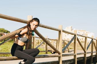 Sporty woman stretching arms at fence