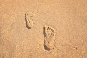 печать ног на песке на пляже с солнечным светом по утрам