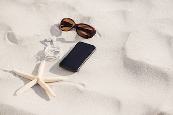 Starfish, sunglasses, headphones and mobile phone kept on sand