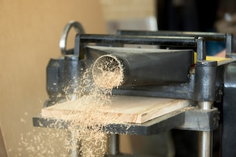 Stationary power woodworking planer processing wooden flooring board, making sawdust