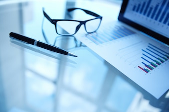 Statistic document with pen and glasses