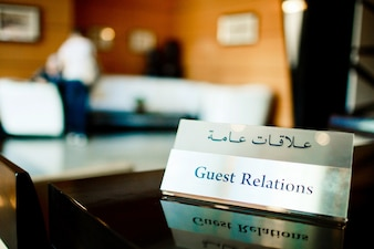 Steel card with lettering 'Guest Relations' stands on the table