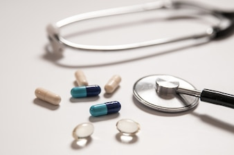 Stethoscope on white background with mix pills isolated