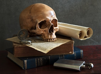 Still life art photography on human skull skeleton with book