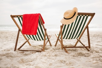 Straw hat and towel kept on beach chairs