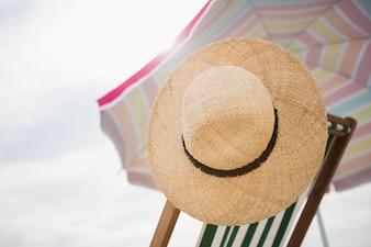 Straw hat kept on empty beach chair