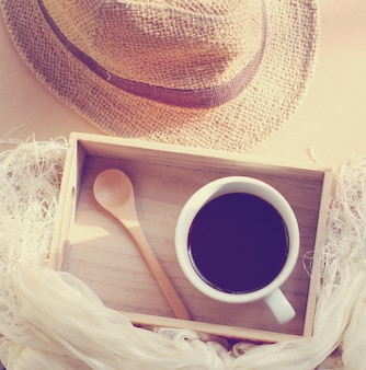 Straw hat with black coffee and spoon on wooden tray, retro filter effect