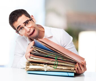 Stressed man looking at a pile of papers