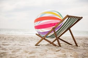 Striped beach ball kept on empty beach chair