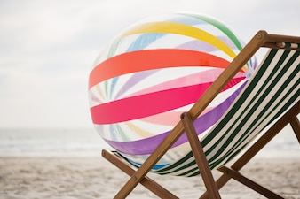 Striped beach ball kept on empty beach chair