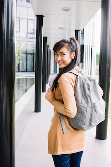 Student girl with backpack turning back