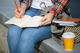 Student girl writing in an open notebook with a pencil