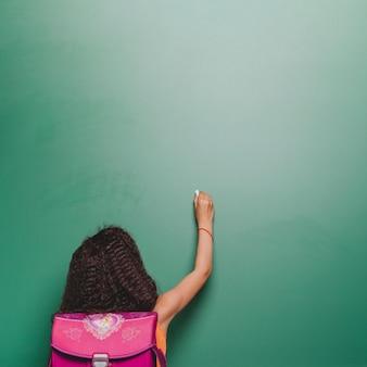 Student girl writing on blackboard