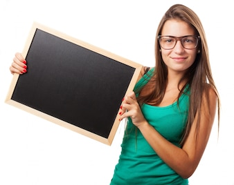 Student with glasses holding a chalkboard