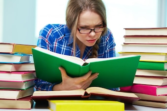 Student with glasses reading several books at once