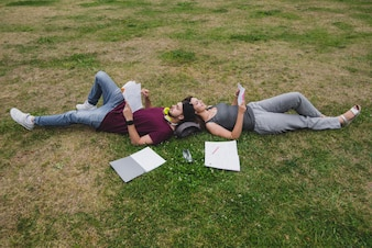 Students lying on grass reading