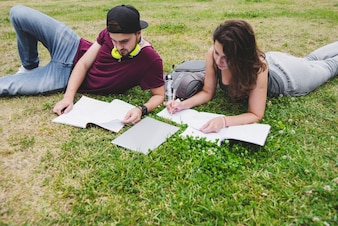 Students lying on grass studying