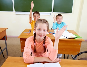 Students raising their hands in the classroom