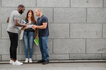 Students standing at gray wall talking