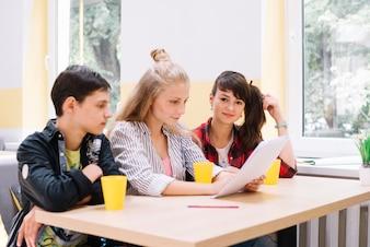 机に書類を持っている学生
