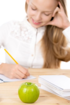 Studying girl and a green apple