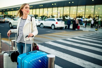 Stunning blonde lady with blue and white suitcases stands before crossing on the street