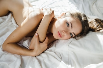 Stunning naked woman with wavy hair lies on white bed in ray of light