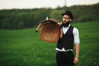 Stylish guy holding a chair in the field