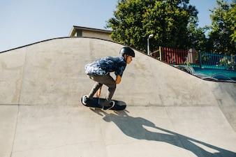 Stylish guy skating outdoors