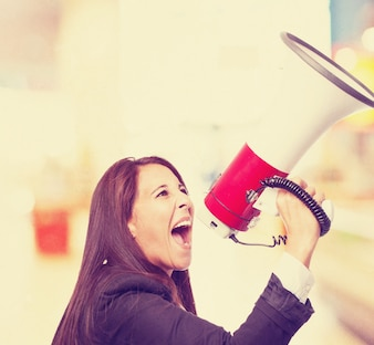 Stylish woman shouting through a megaphone