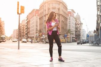 スタイリッシュな女性が歩道にコーヒーを持ち帰る