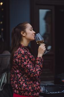 スタイリッシュな若い女の子は、夏のテラスで通りのカフェでワインを飲みます。長い髪の女の子は夏の夜にワインを楽しむ。ポートレート。閉じる