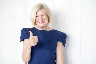 Successful senior businesswoman showing thumbs up