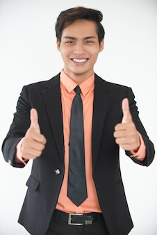 Successful young businessman showing thumbs up
