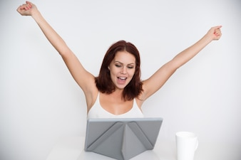 Successful young woman rejoicing at digital tablet