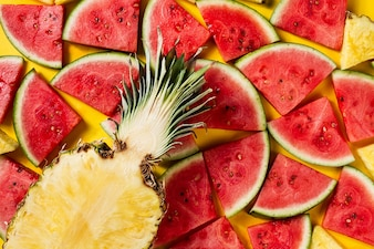Summer concept. Conceptual. Tasty appetizing slice of pineapple with watermelon slices on yellow bright vibrant background with wooden letters Summer. Flat Lay.
